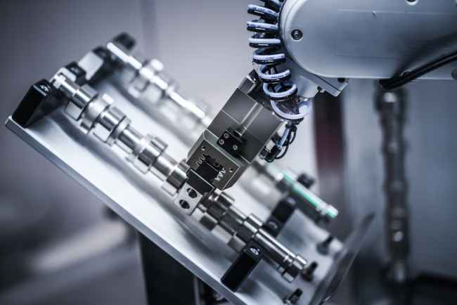 A photo of a robotic arm working on a factory floor.