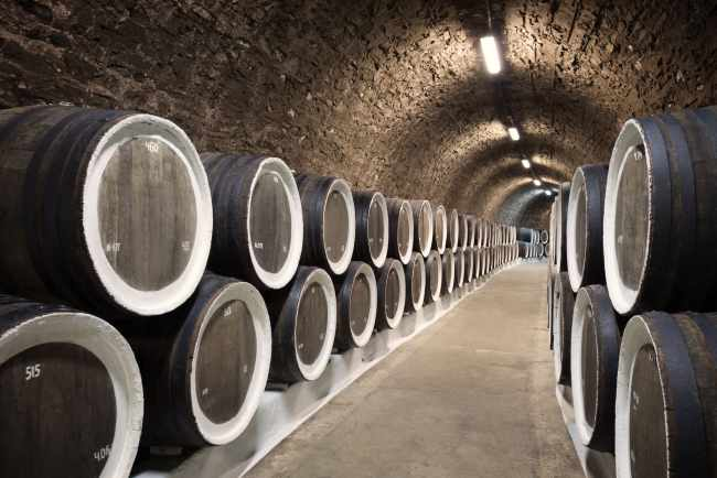 A picture of barrels in the wine cellar, one industry affected by US-China Trade.