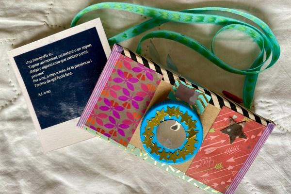 camara de fotografiar de cartró i decorada amb papers, cintes, gomets i un tap de plàstic