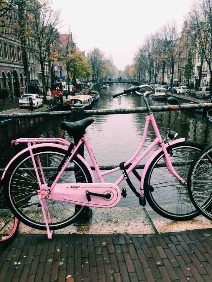 A pink bike in Amsterdam...pops of pink color line the bridges of Amsterdam's canals! The cheapest hotel for an instagram- and eco-friendly stay in Amsterdam: Ecomama Hotel Amsterdam is cozy, sustainable and made my time in Amsterdam special.