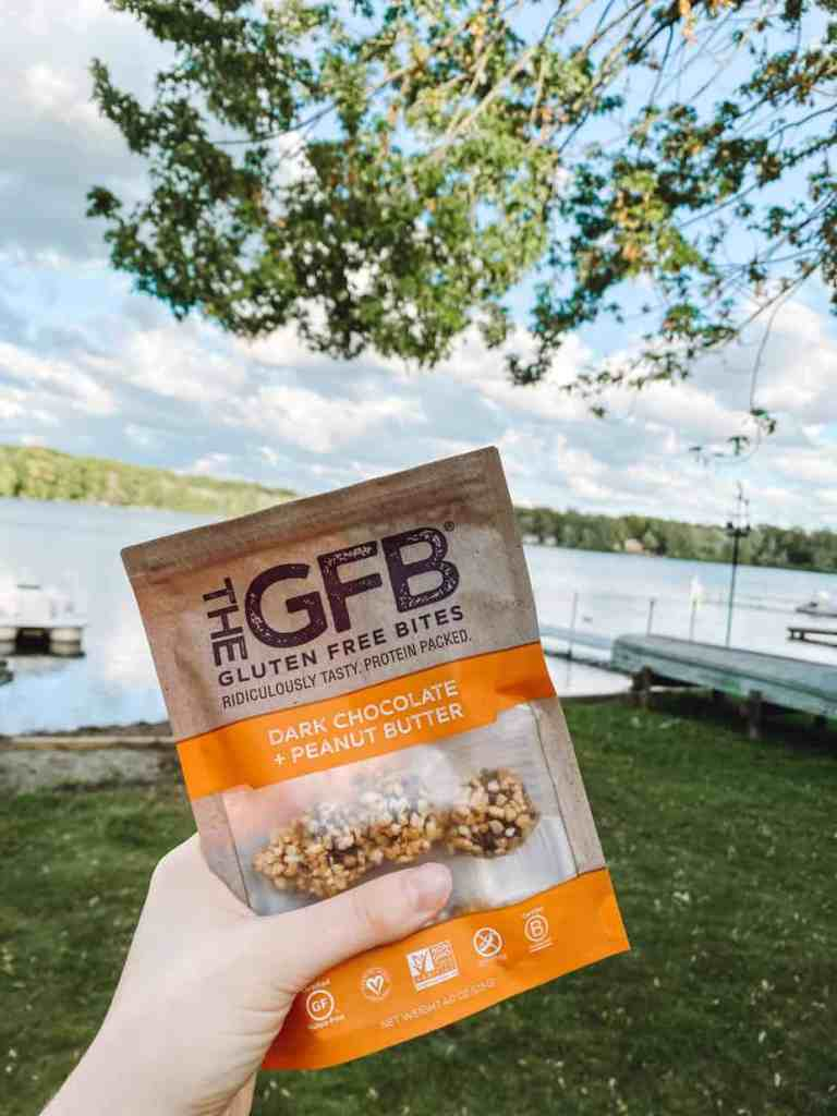 Dairy free gluten free snacks on the go - a bag of GFB gluten free bites being held up in front of a lake.
