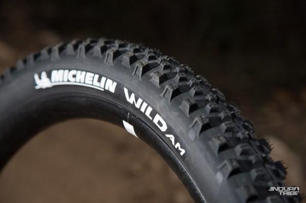 Le Michelin Wild AM propose lui un profil nouveau, aperçu jusqu'ici sur les pneus prototypes des pilotes de la marque. Crampons plus proéminents sur tout la surface de contact au sol...