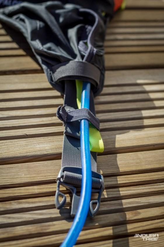 Sur la ceinture, le tuyau peut sortir à gauche ou à droite, et venir se clipser sur l'avant. Suffisamment long pour atteindre la bouche, il l'est presque trop pour tenir en place sans pendre. L'astuce consiste à glisser la tétine dans le dos, entre le maillot et la poche, pour éviter qu'elle ne se balance dans le vide.