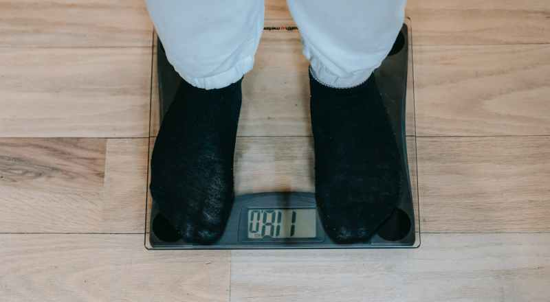 crop obese person standing on weighing scale