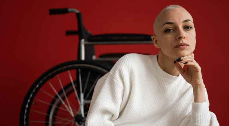 woman with shaved head against wheelchair on red background