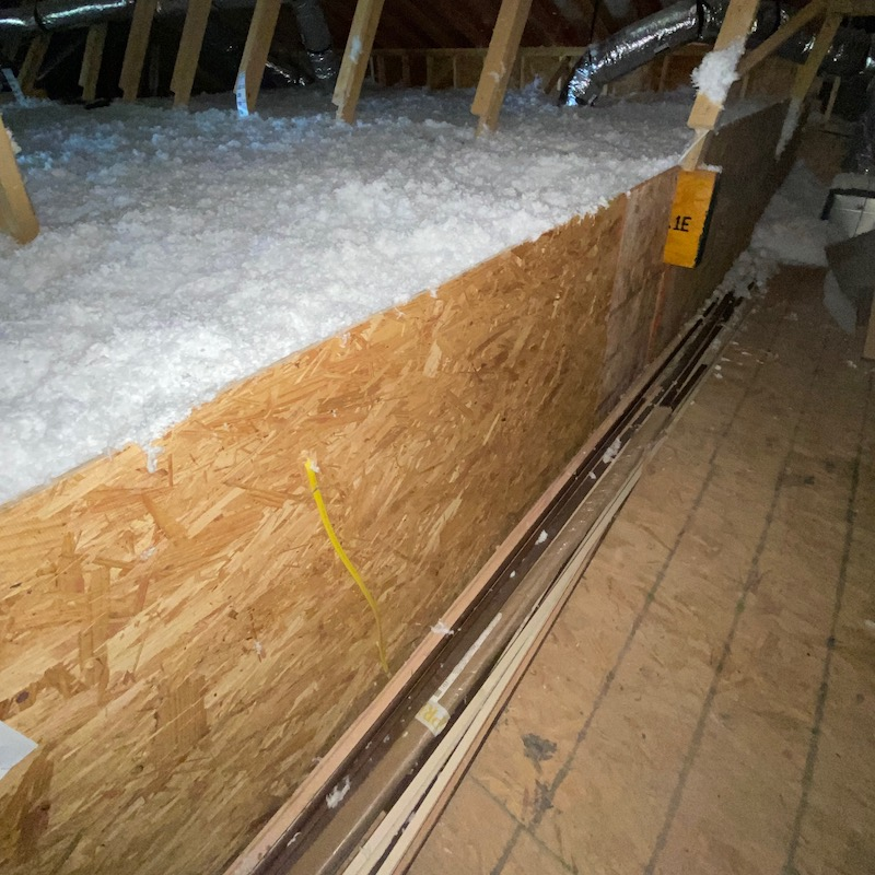 An attic kneewall sheathed with OSB and extended upward to create an insulation dam [Photo credit: Dave Yelovich, Tilson Homes]