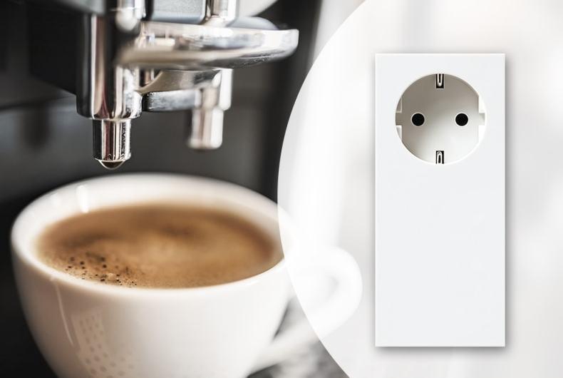 Kaffeetasse unter einer Kaffeemaschine. Rechts im Bild ist eine Steckdose abgebildet.