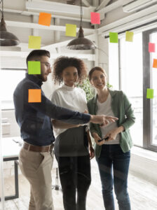 Happy young mixed race diverse business people managers standing near glass wall with pinned colorful sticky notes, managing workflow or organizing project processes together in modern office.