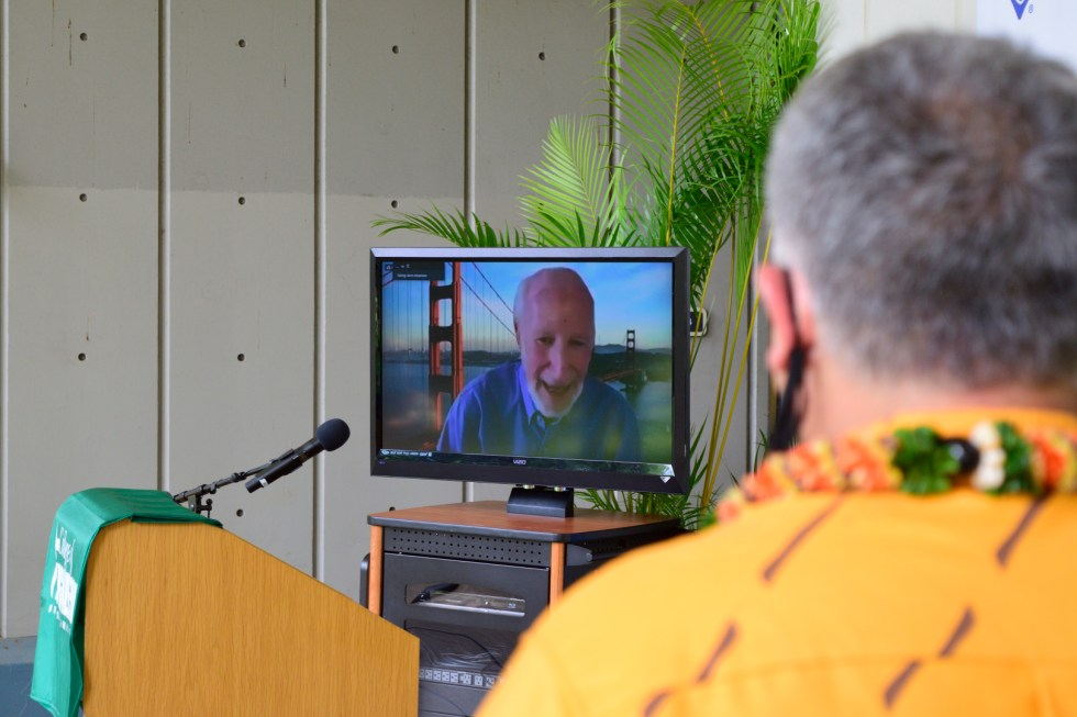 Dean Morioka Looks On While Norm Abramson Addresses The Audience.