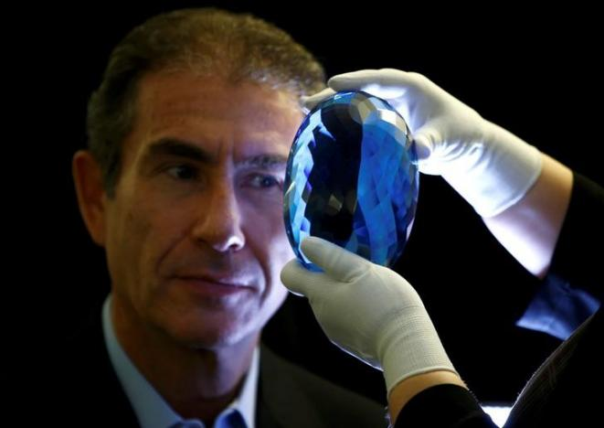 Philanthropist Maurice Ostro looks through his Ostro stone, the largest known blue topaz stone, for media at the Natural History Museum in London