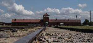 fachada de una construccion con tejado naranja y una torre en el centro visto desde lejos, desde un campo abierto con vías de tren