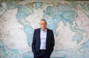 El ministro de traje azul y camisa clara sin corbata posa delante de unmural con el mapa del mundo