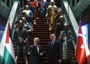 El presidente turco a la derecha y Abbas a la izquierda se dan la mano posando para la cámara a pie de una escalera con moqueta roja con soldados con armaduras, escudos y uniformes militares de época a ambos lados de los escalones