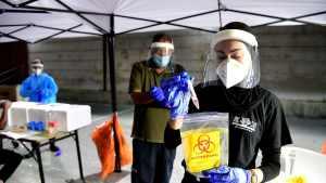 Laboratorista de Israel manipula una muestra nasofaringea para una prueba de coronavirus