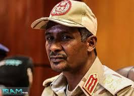 rostro de militar con uniforme beige claro, gorra con un escudo y detalles en rojo. persona de color, mira de costado girado hacia la cámara. Lleva bigote