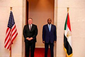 Dos hombres de pie con traje oscuro a la entrada de un sitio oficial , a la izquierda una bandera de Estados Unidos, a la derecha la de Sudán, Alfombra roja.