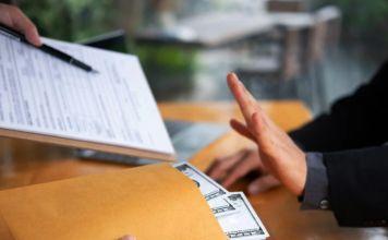 un sobre del que asoman billetes, junto a unos documentos y un lapicero para firmarlos, una mano izquierda hace un gesto de rechazo, la dercha está apoyada en la mesa
