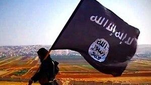 Bandera de ISIS cargada por una persona vestida de negro en el desierto