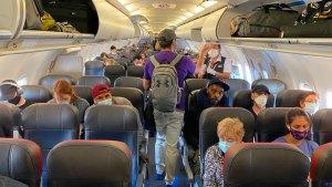 personas en los asientos de un avión comercial con cubrebocas