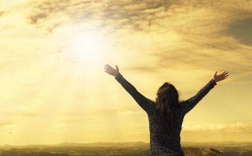 Una mujer levantando kos brazos al cielo