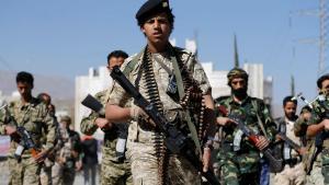hombres jóvenes fuertemente armados, de uniforme militar, desfilando