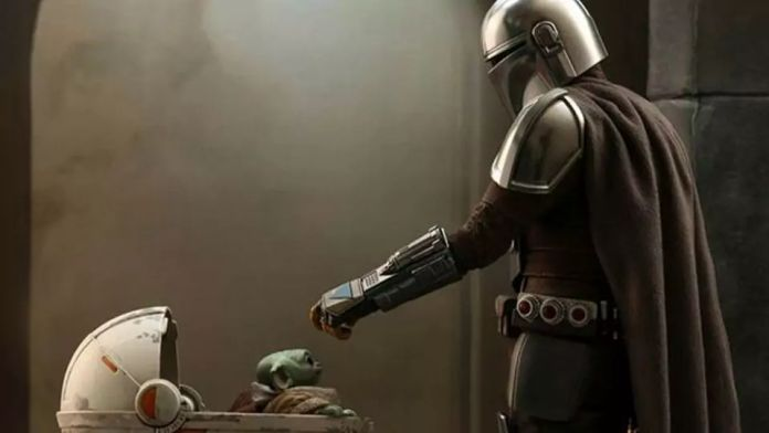 Mandalorian 2 - Mando de la serie Mandalorian de Disney+ acaricia a Baby Yoda en su carreola