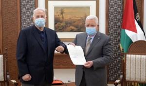 El presidente palestino Mahmoud Abbas y un funcionario