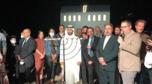 varias personas de pie frente a una menorá de altura casi humana con un representante árabe con su atuendo típico