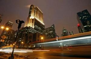 imagen nocturna de una zona de una ciudad con edificios iluminados tomada desde abajo