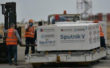 trabajadores descargan cajas de la vacuna Sputnik V sobre un palet