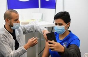 Una mujer con mácara recibe la vacuna contra COVID-19