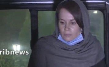 imagen de una mujer occidental con ropa tradicional musulmana, la mascarilla bajo la barbilla y llos ojos mirando hacia abajo en una entrevista