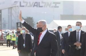 el primer ministro de Israel saluda con el brazo derecho en alto y mascarilla,