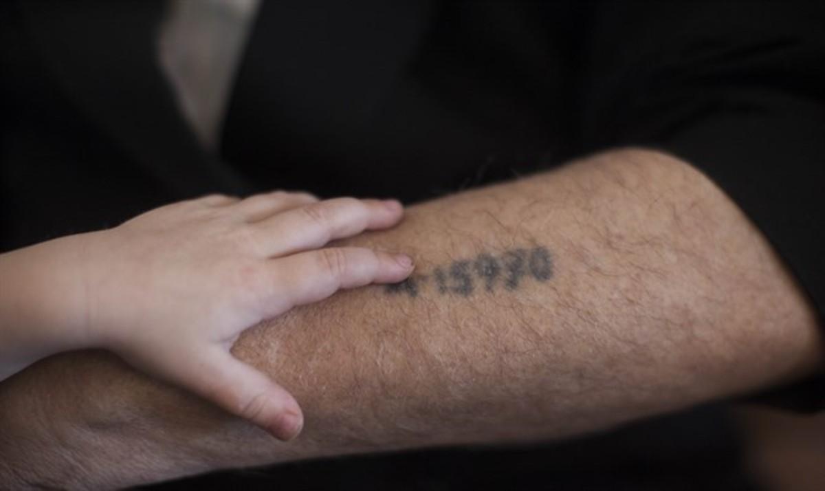brazo tatuado con un número con una mano infantil encima