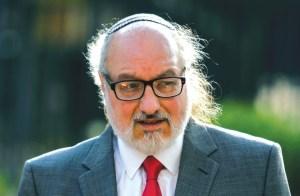 rostro de un hombre con kipá, lentes y barba blanca de fente a la cámara mira ligeramente hacia la derecha