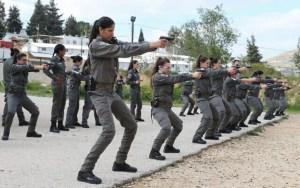 mujeres con uniforme gris de policiá en práctica de tiro