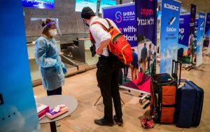 hombre alto con kipa y mochila habla con una mujer equipada con protección contra COVID-19