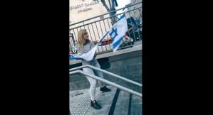 Mujer destruyendo una bandera de Israel