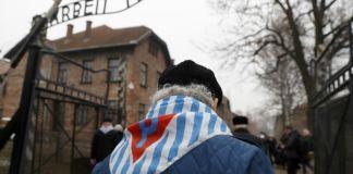un hombre de espalda con un panueño a rayas blanco y azul y la letra hebrea shin (de Shoá) en rojo atraviesa la entrada de Auschwitz del que se ve el cartel Argeit macht frei (El trabajo te hace libre)