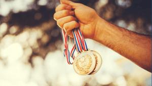 Medallas olímpicas en la mano de una persona ser mejores. No primeros