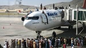 Afganos trepan sobre un avión tras la toma de Afganistán por parte del Talibán
