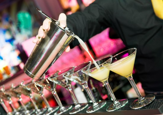 barman-pouring-a-row-of-drinks-550x387