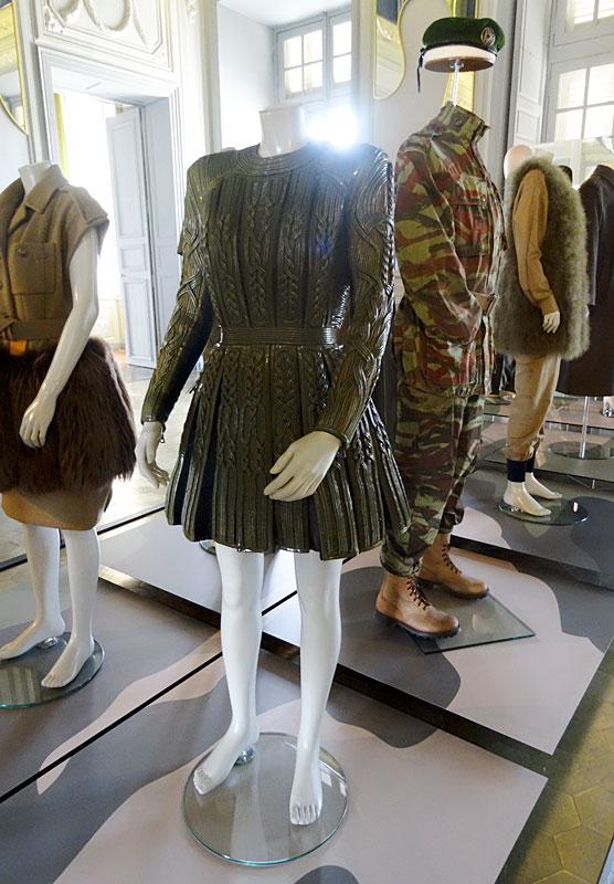 Robe courte de couleur kaki, inspirée des cuirasses de gladiateurs d'Olivier Roustein pour Balmain (Prêt à porter, automne/hiver 2014/2015) et Tenue de combat parachutiste entre 1956 et 1962, emblématique de la guerre d'Algérie avec son célèbre béret vert