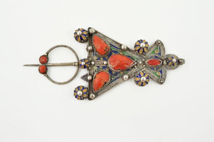 Détail d'une paire de fibules ibzimen , Algérie, Kabylie, vers 1900 Argent et émail Mucem © Mucem. En Kabylie, les fibules ibzimen sont offertes par paire aux jeunes femmes en cadeaux de mariage. Elles servent à fixer les deux parties du costume traditionnel, la robe drapée et la mante. Les bijoux font partie de la dot de la jeune fille. Dès l'enfance, ses proches commencent à lui constituer sa parure. Plus tard, lorsqu'elle se fiance, les parents du futur mari lui offrent plusieurs bijoux, qu'on exhibe devant les invités et dont on fait connaître le prix.