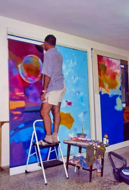 Contemporary artist Enriquillo Amiama workinng at his art studio in a commissioned mural painting for a international corporate company.
