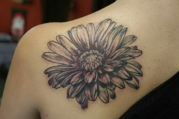 black and white single daisy tattoo on back shoulder blade