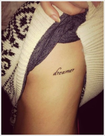 small lettering dreamer tattoo on ribs for girls