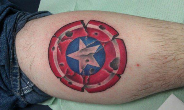 worn captain america shield tattoo on leg