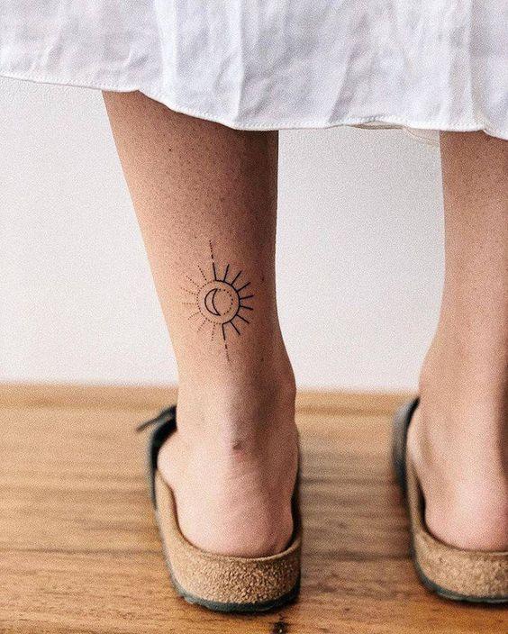 minimalist sun and moon tattoo design on leg