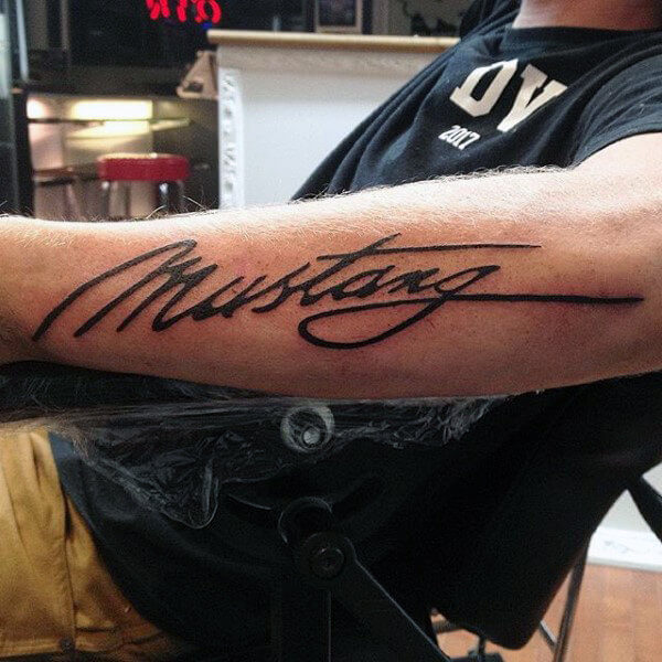 mustang script font tattoo on arm